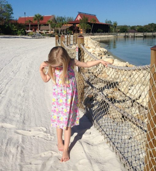 little girl standing in the sand
