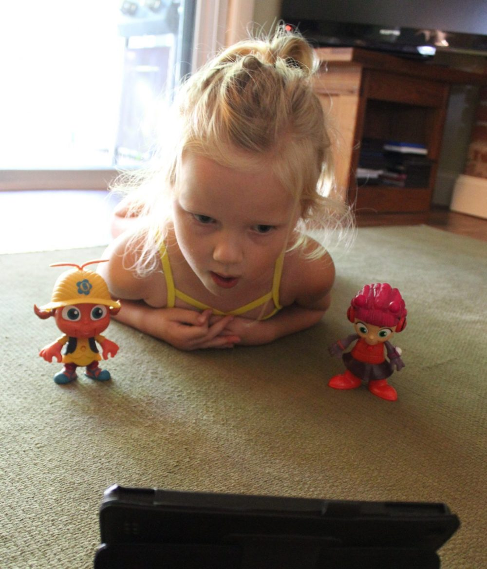 little girl playing with beat bugs toys