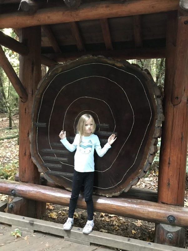 little girl standing in front of a tree ring