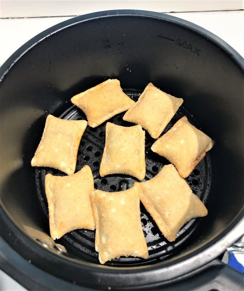 air fryer with pizza rolls arranged inside in a single layer