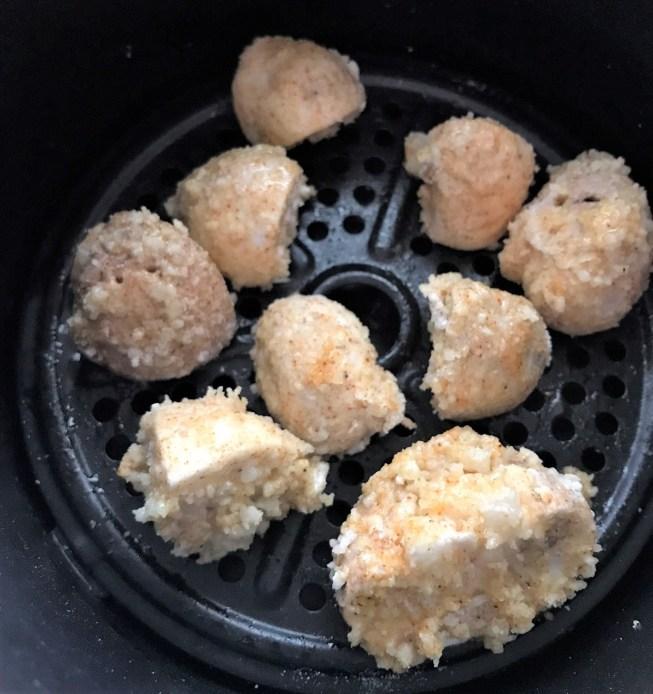 mushrooms arranged in a single layer in an air fryer basket