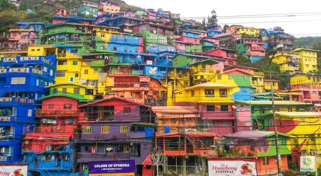 """Known as the """"Valley of Colors"""", Stobosa Hillside Homes is a community of rows after rows of 200 colorful houses at the hillside of La Trinidad, Benguet. It is an artwork village desinged by the Tam-awan Village group as part of Rev-Bloom Urban Redevelopment Tourism campaign in 2016. To get here, go to Magsaysay Street and take a jeepney with TOMAY signboard. Tell the driver to drop you off where there are colorful houses. Fare is P10. Rating: 2/5"""