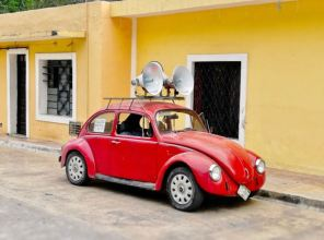 An old red VW beetle available for hire as a public address system in Izamal, Mexico