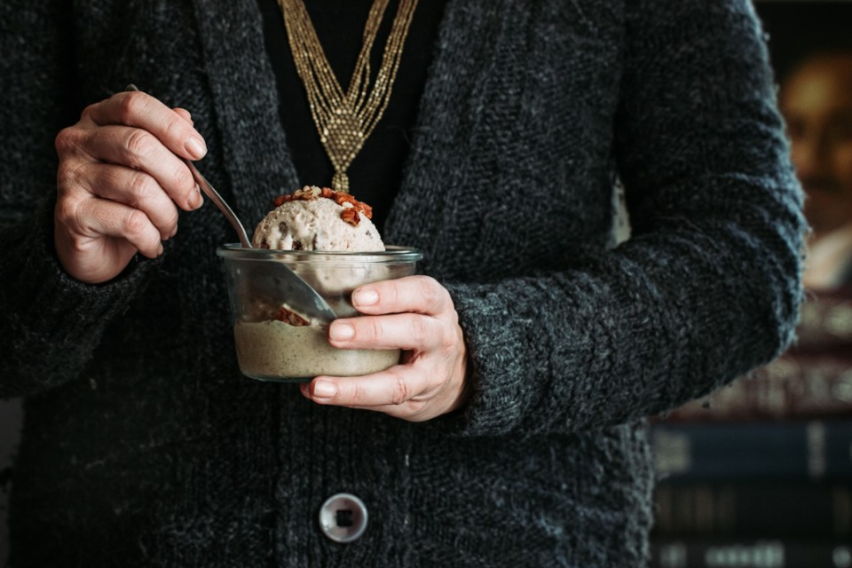 woman in a cozy sweater eating a scoop of pumpkin whiskey gelato
