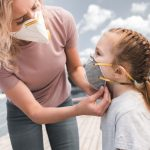 mother wearing protective mask on daughter on bridge, air pollution concept