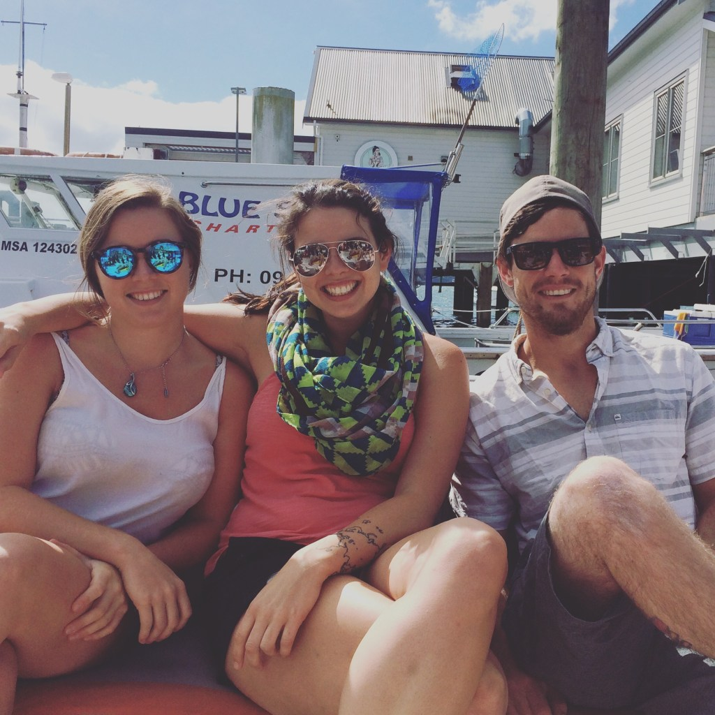 two girls and one guy on a boat