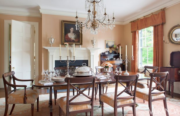 Luxury Salmon colored walls in the dining room have a golden glow at night s mahogany dining table and chairs upholstered in Christopher Hyland silk linen and