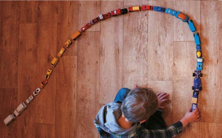Child creating a spiral made out of toy cars arranged by colours. Copyright Autistica