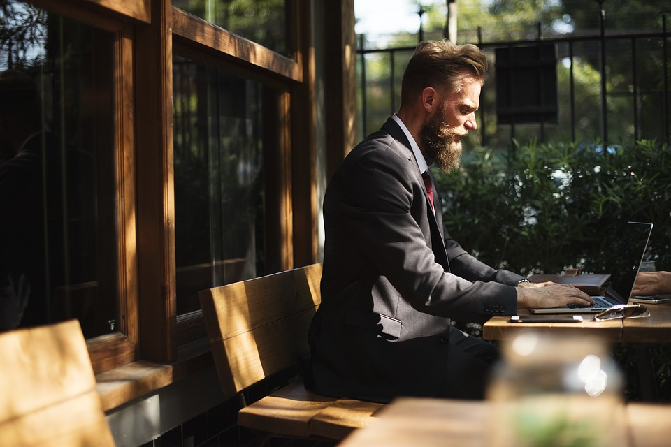 man with beard and suit working outdoors