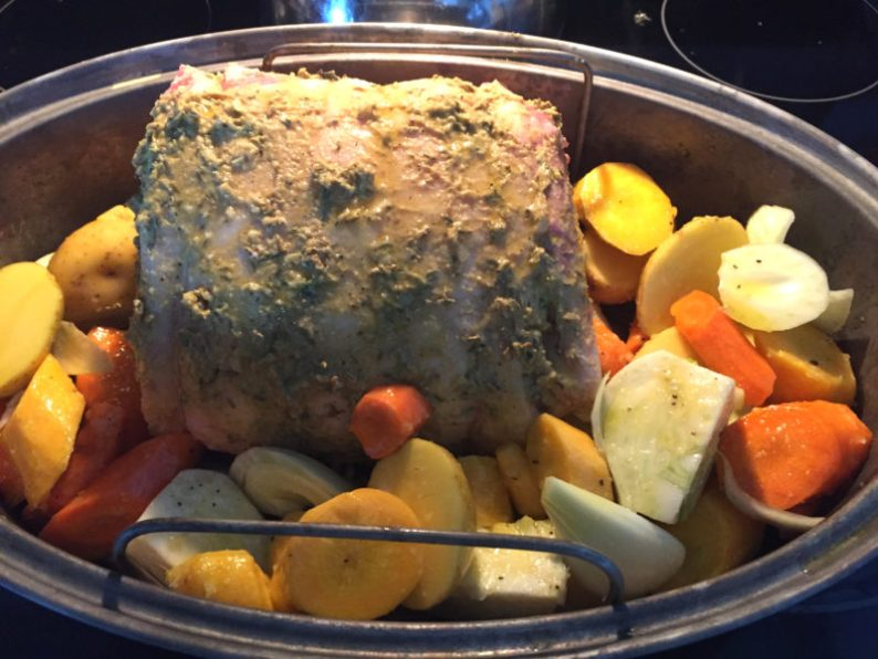 Pork ready for roasting with potatoes and carrots, moistened lightly with olive oil to roast along with meat; stir occasionally in pan juices to keep moist