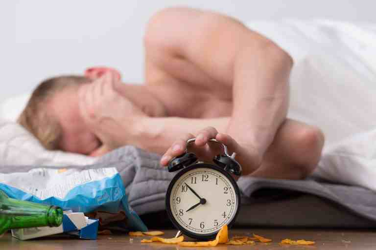 Man with hangover is waking up and shutting off alarm