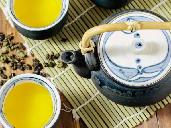 Cup of Japanese green tea with teapot on wooden table. <br></noscript> (Source of featured image: Fixma: 49987256/ 123rf.com)