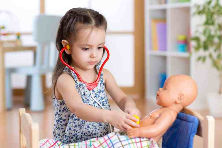 child playing doctor with doll