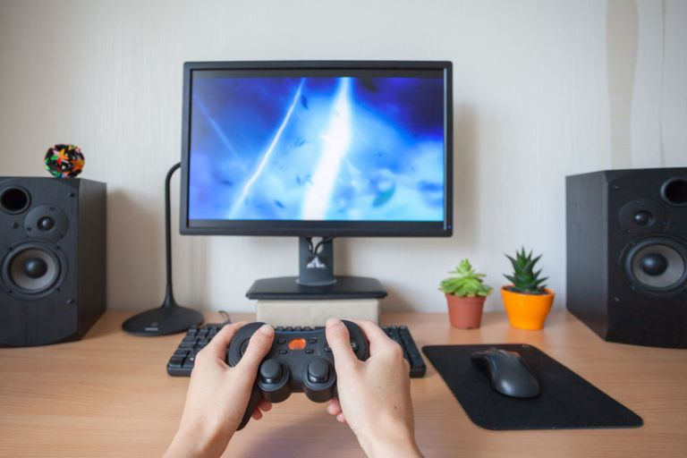 Playing video game with gamepad, close-up