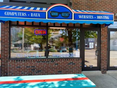 Good Geeks storefront in a brick building with blue awning.