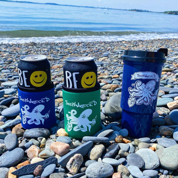 Shipwreckd beer koozies in blue and green with kraken on front and shipwreckd navy blue travel mugs