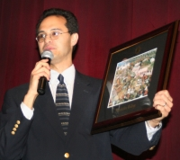 Dr. Edward Sri holding a picture of Benedictine College's campus, where he was a professor for years.