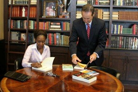 President Minnis gets Immaculee to sign a few more books.