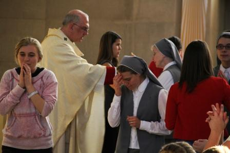 Archbishop Joseph Naumann distributing communion to students ... and sisters.