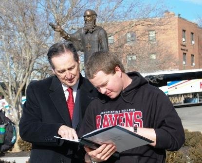 St. Benedict overlooks President Stephen D. Minnis and senior Andrew Green as they review the