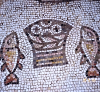 At the Holy Land Church of the Multiplication of the Loaves a mosaic depicts four loaves. The fifth is in the tabernacle.