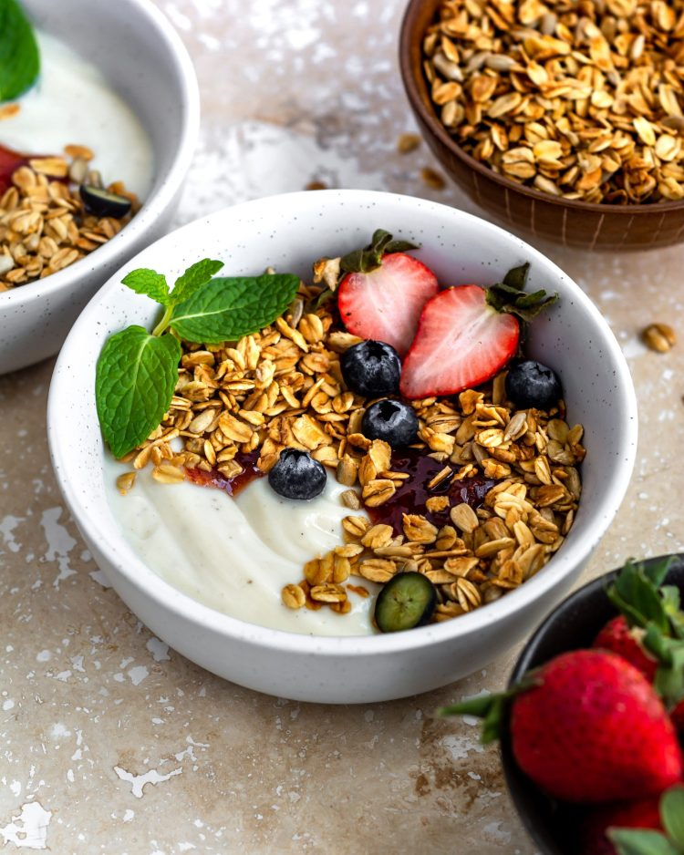nut free granola in a white bowl with fresh fruits and soy yogurt
