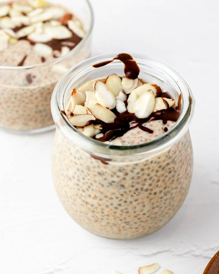 almond butter chia pudding in a jar with melted chocolate and raw almond slices