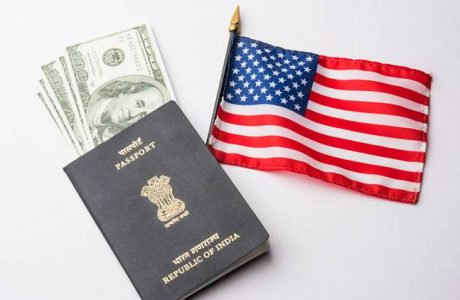 concept showing Indian passport with US currency notes or Dollars with american flag in the background, applying for US / american tourist or H-1B visa or travel visa