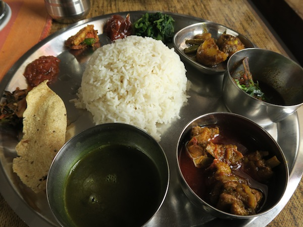 Thakali Khana set- Rice, Black lentil daal, Chicken curry, Fish curry, Seasonal vegetable curry, Stir-fried spinach, Radish pickle, Timur-Tomato chutney, Lapsi pickle, Gundruk pickle and Papad
