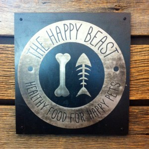 Metal sign logo for The Happy Beast, a natural pet store in Lafayette, CO