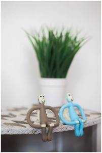 two matchstick monkey teething toys resting on a table.