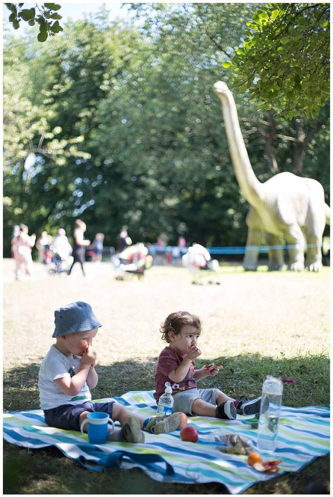 toddlers eat a picnic in the shadow of jurassic kingdom dinosaurs