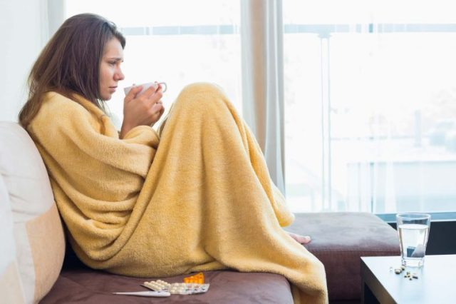 Sick woman wrapped in a blanket with a cup of tea.