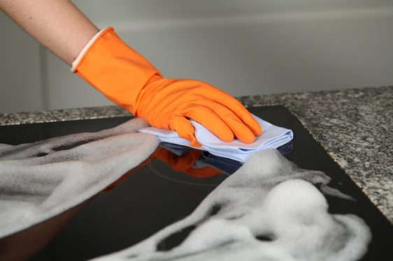 Hand in protective glove cleaning a stove