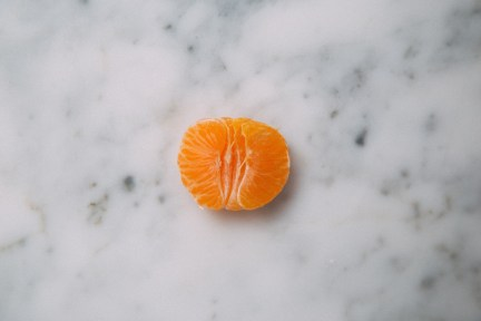 peeled half of an orange tangerine sitting on a counter.