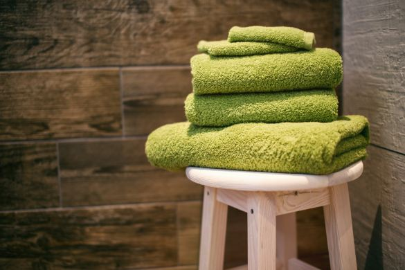THREE GREEN TOWELS SITTING ON A BAR STOOL