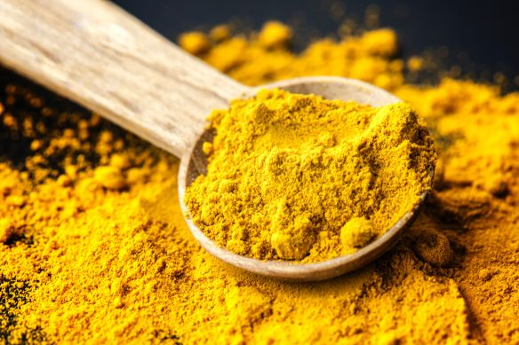 POWDERED YELLOW TURMERIC AND SPOON
