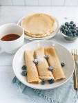 Plate of Norwegian Pancakes with powdered sugar, blueberries, and coffee