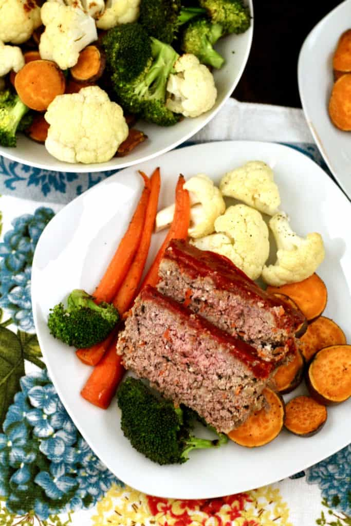 Slices of healthier bison meatloaf with roasted vegetables