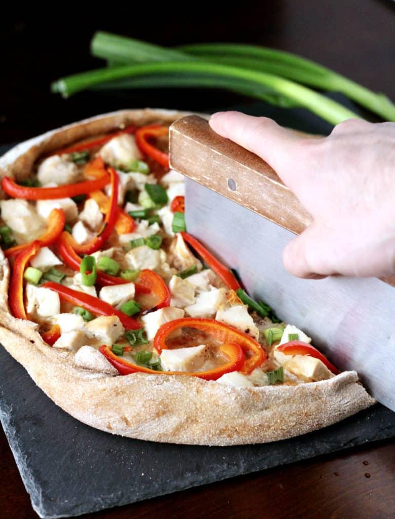 Slicing Thai chicken pizza