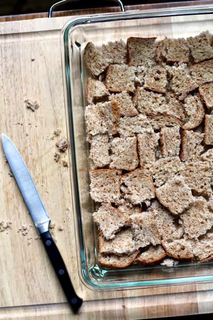 Placing bread cubes in baking pan