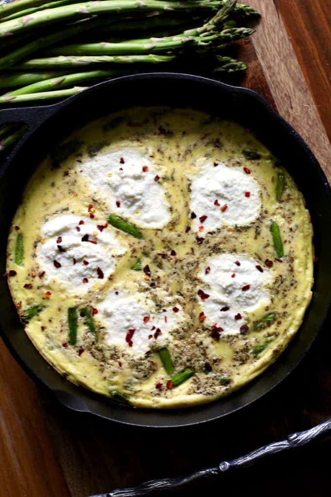 Simple asparagus frittata with ricotta cheese in a cast iron skillet