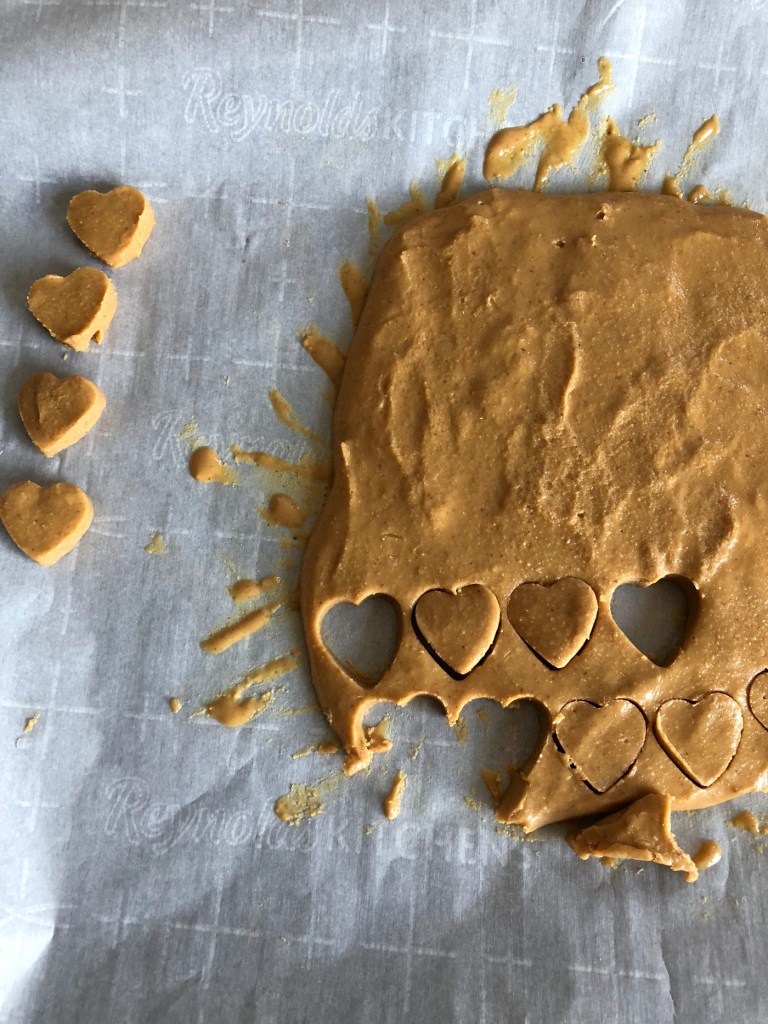 Cutting out hearts into peanut butter and coconut flour mixture