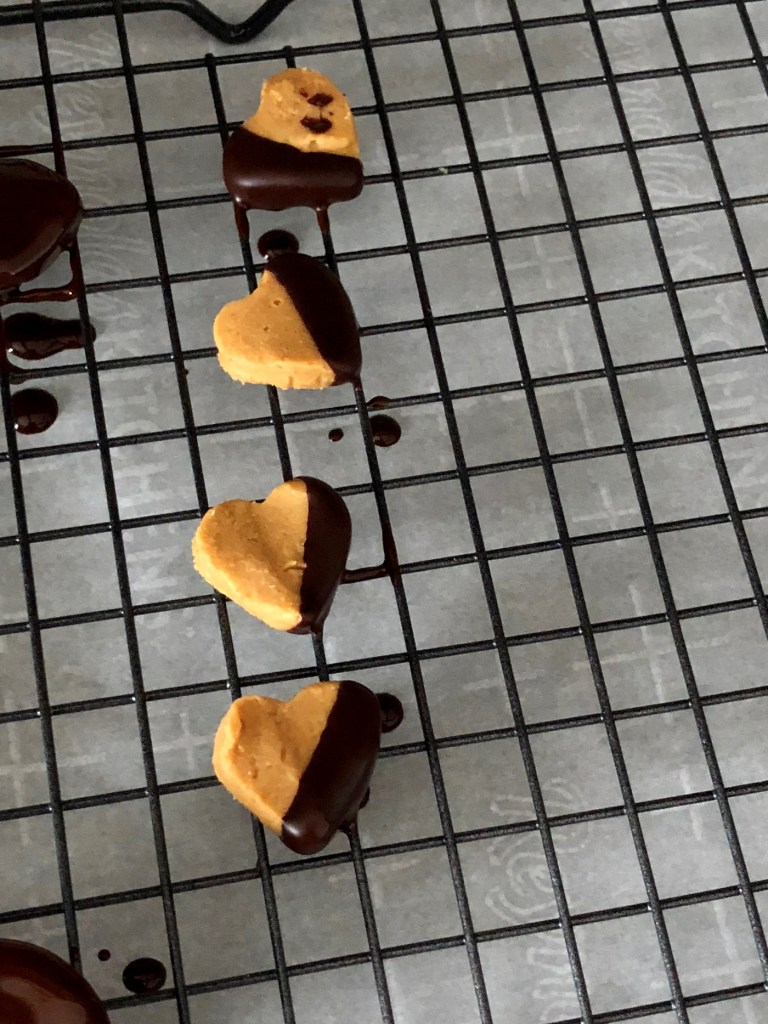 Chocolate dipped peanut butter hearts on cooling rack