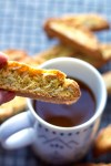 Dunking cardamom biscotti with orange zest into coffee