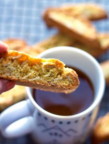 Dunking cardamom biscotti with orange zest into coffee