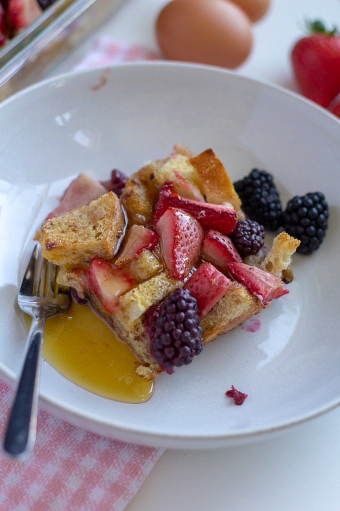 Slice of lightened up berry French toast casserole with maple syrup