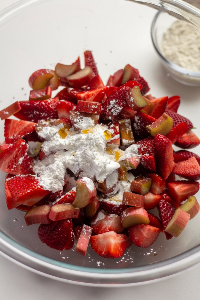 Adding corn starch and maple syrup to strawberries and rhubarb