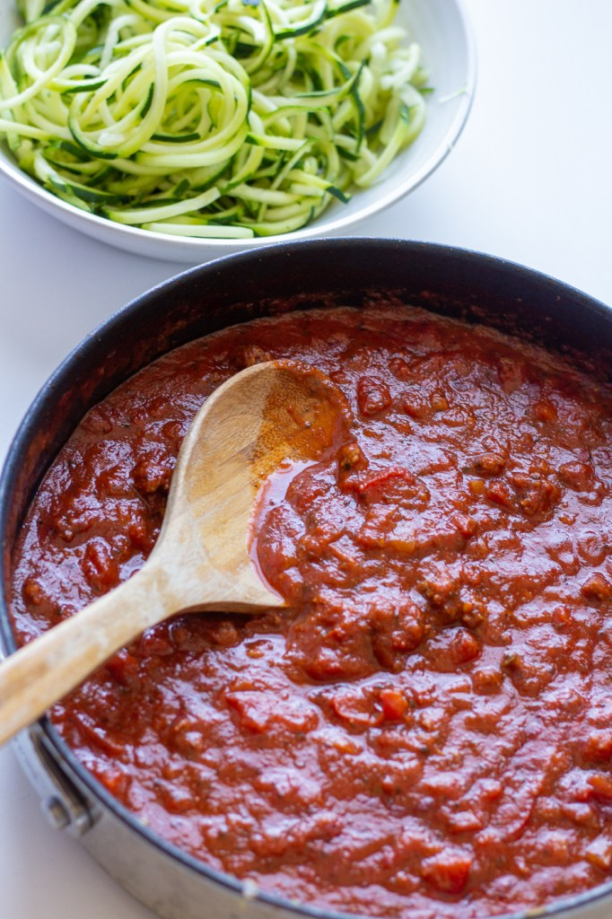 Saucepan of homemade meat sauce with wooden spoon and zoodles