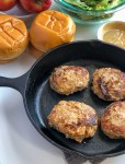 four cooked apple cheddar turkey burgers in a cast iron skillet with brioche buns in the background
